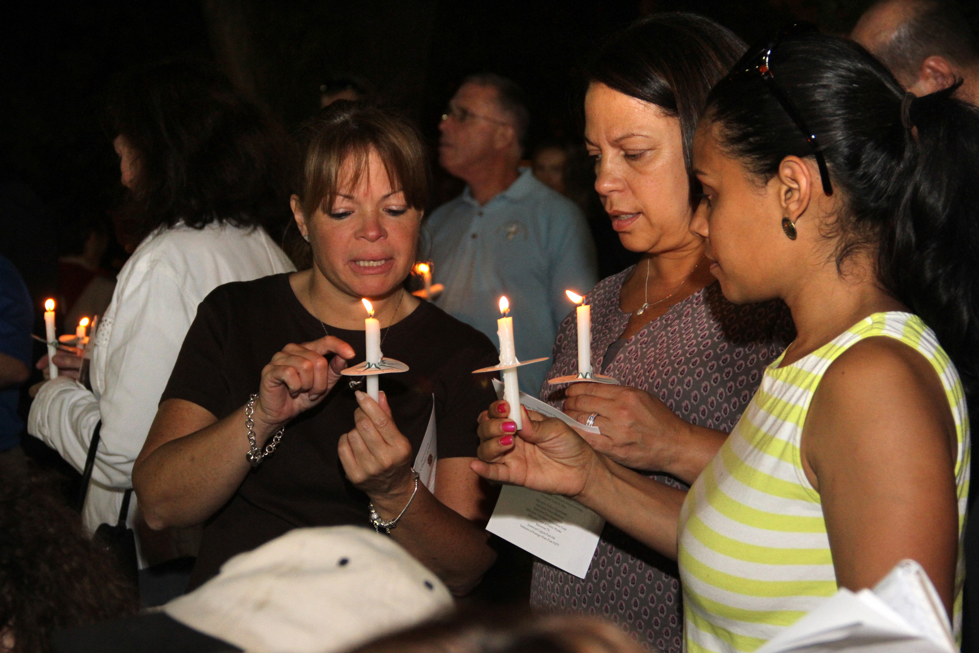 Lissette Ortolani, Sonia Mangual and Miriam McDaniels raised their candles at the Sept. 11 memorial service.