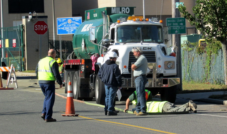 Workers clean up oil that accidentally spilled from a truck during a Wednesday morning delivery to the plant.