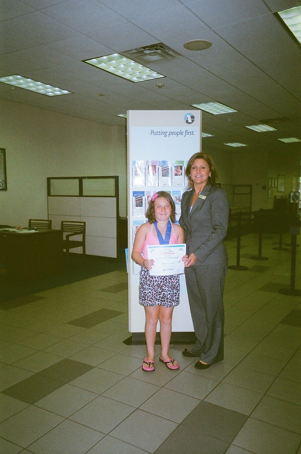 Stephanie Amato, 9, of Franklin Square, was all smiles when she was presented with an award for her winning essay by Astoria Federal Savings Bank's Franklin Square Branch Manager Elaine Russo.