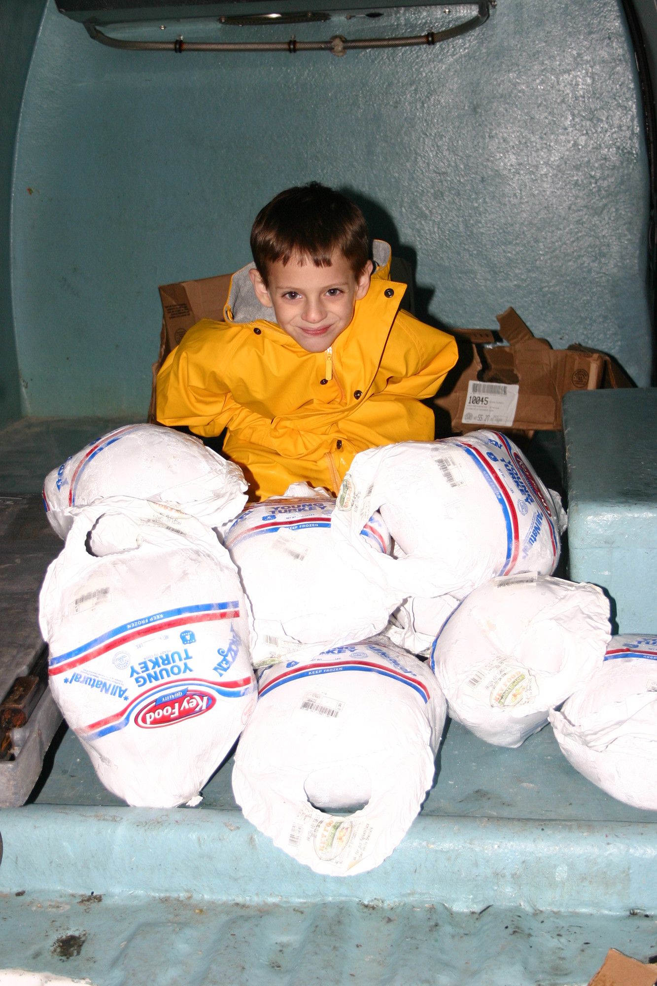 Stefen Rosner, when he was 7, with frozen turkeys his family purchased in 2005 to deliver to Island Harvest. He and his twin brother, Jamie, of Bellmore, now 15, have organized an annual Yom Kippur food drive at East Meadow