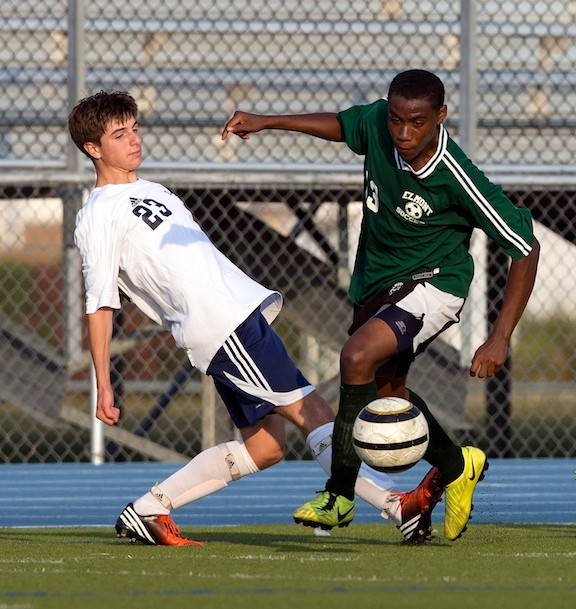 Elmont's Johnathon Davis, right, makes a move around Oceanside's Joseph Schindler during the opener for both teams.