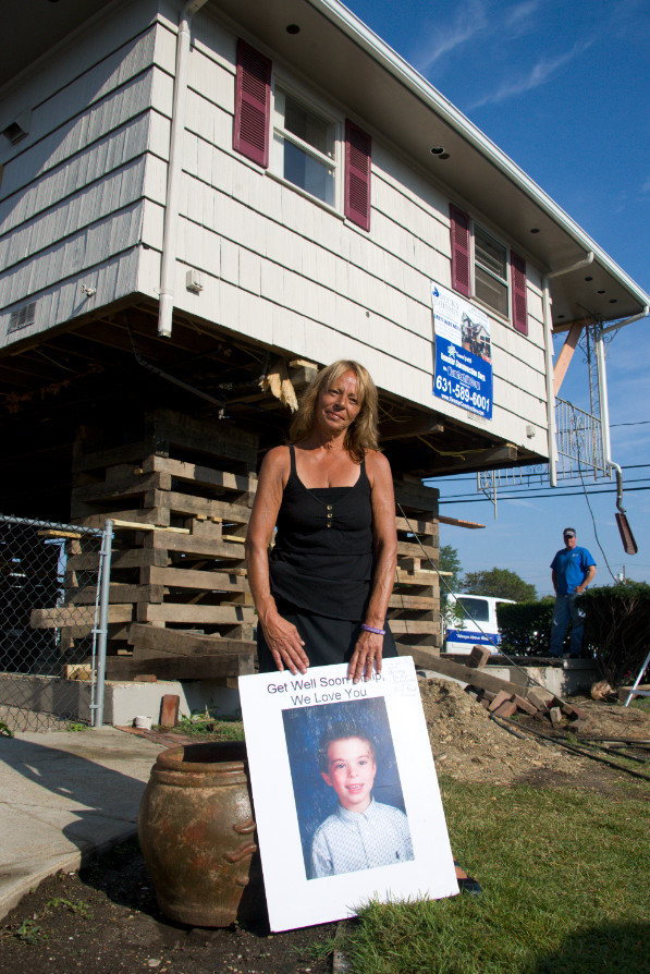 Anna D'Amaro sands in front of her Island Park home with a photo of her nephew, Philip, who died of cancer a week prior to Sandy.