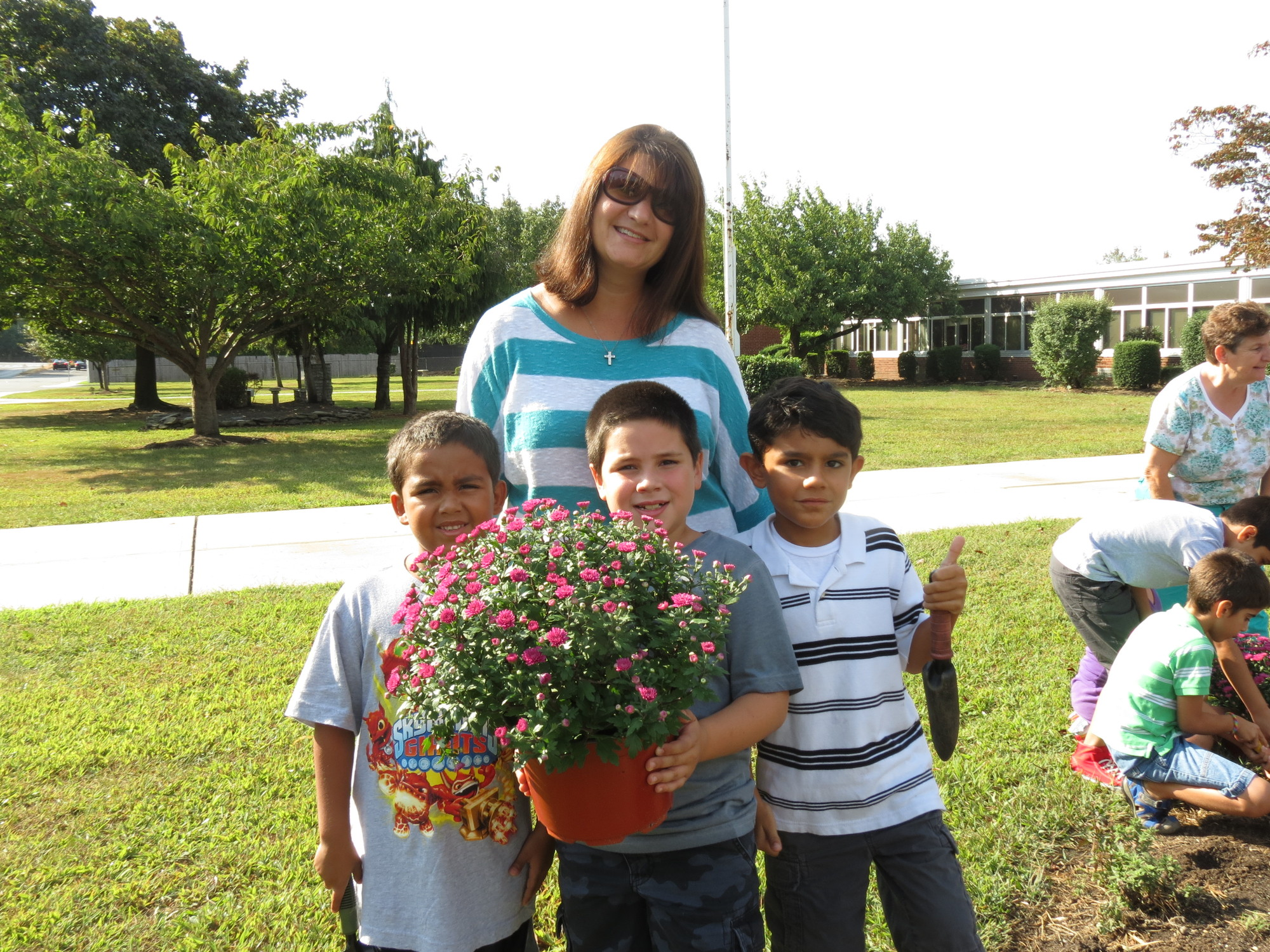 Meadowbrook PTA member Margaret Rosenthal assisted second-graders with planting an array of fresh asters and mums during the gardening event.