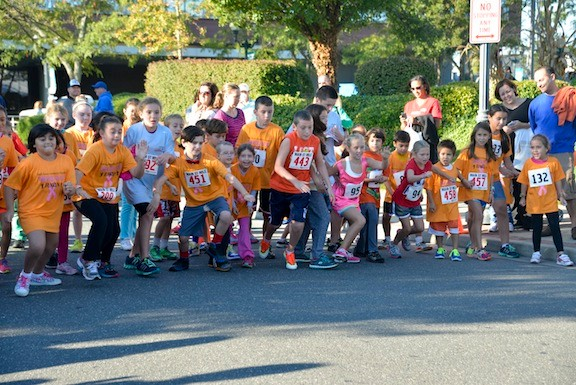 The competitors in the fun run take off from the starting line.