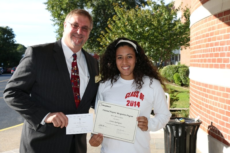 West Hempstead High School Principal Dan Rehman awarded Commended Student Jaime Rodriguez with a certificate that recognized her academic strides in qualifying for the 2014 National Merit Scholarship Program.