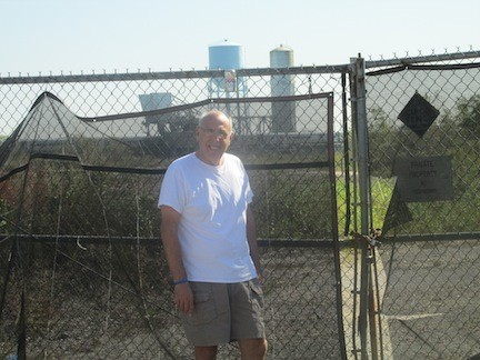 Harbor Isle resident Nicholas Mela in front of the gate of the former Cibro oil transfer site. If developers have their way, the site may one day hold a mixed-use development consisting of 32 condominiums and 140 rental apartments. Mela opposes it.