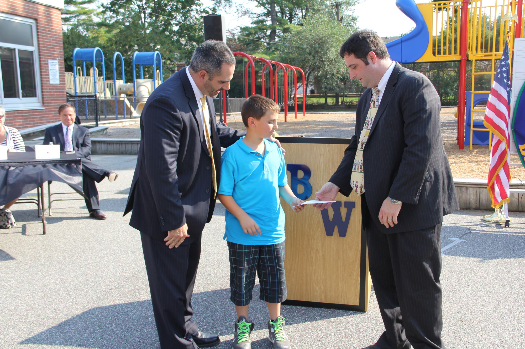 Barnum Woods fourth-grader Nicholas Goldstein and Principal Gregory Bottari, left, presented Francis X. Hegarty Principal Jacob Russum with an $18,500 donation last Friday.