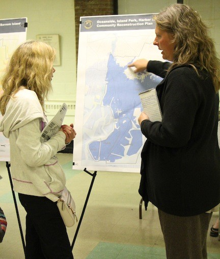Jennifer Street, right, with a map of Oceanside, Island Park, Harbor Isle and Barnum Island, discussed various options for rebuilding the area and making it more sustainable with resident Ellen McDermott.