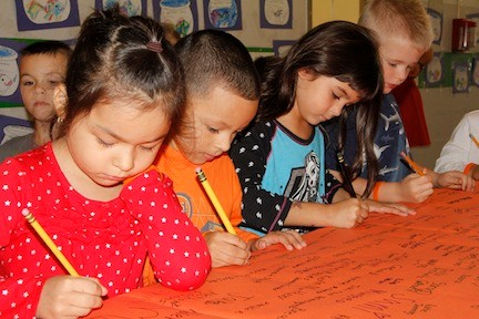 By signing a banner in McVey Elementary School on Oct. 9, Allyson Kay