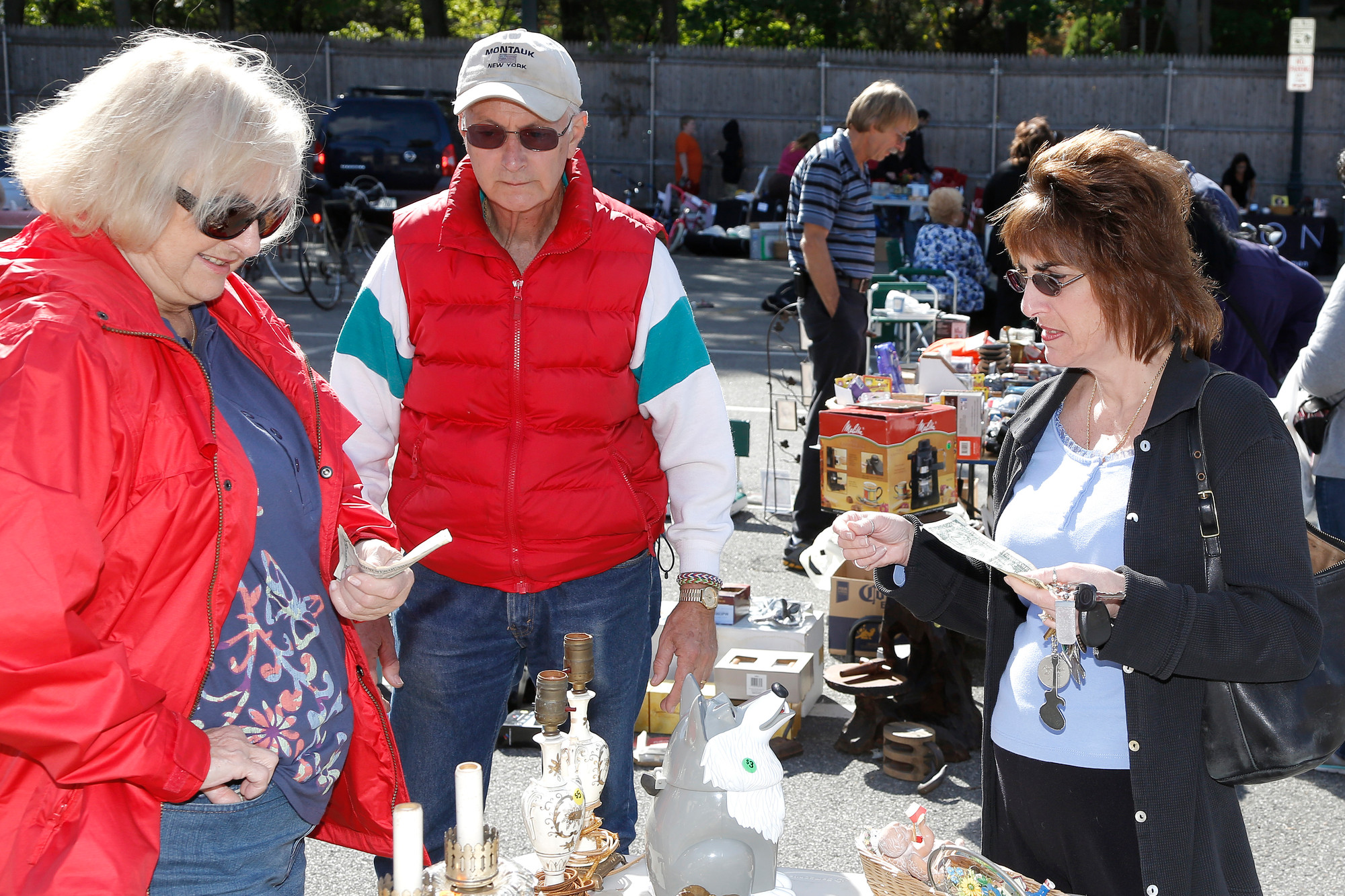 Doreen Mamay, (r)   from West Hempstead,  look over the offerings at Linda and Sal Furnari's table.