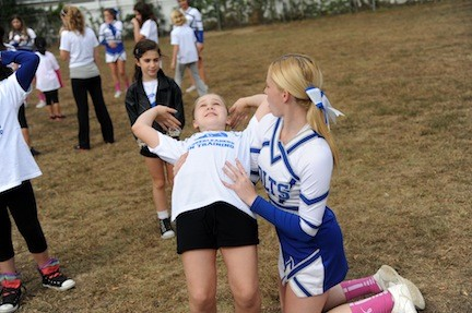 Kaitlyn Cunningham, 17, helped Michaela Brown, 9, practice a back flip at Calhoun High School's Homecoming festival.