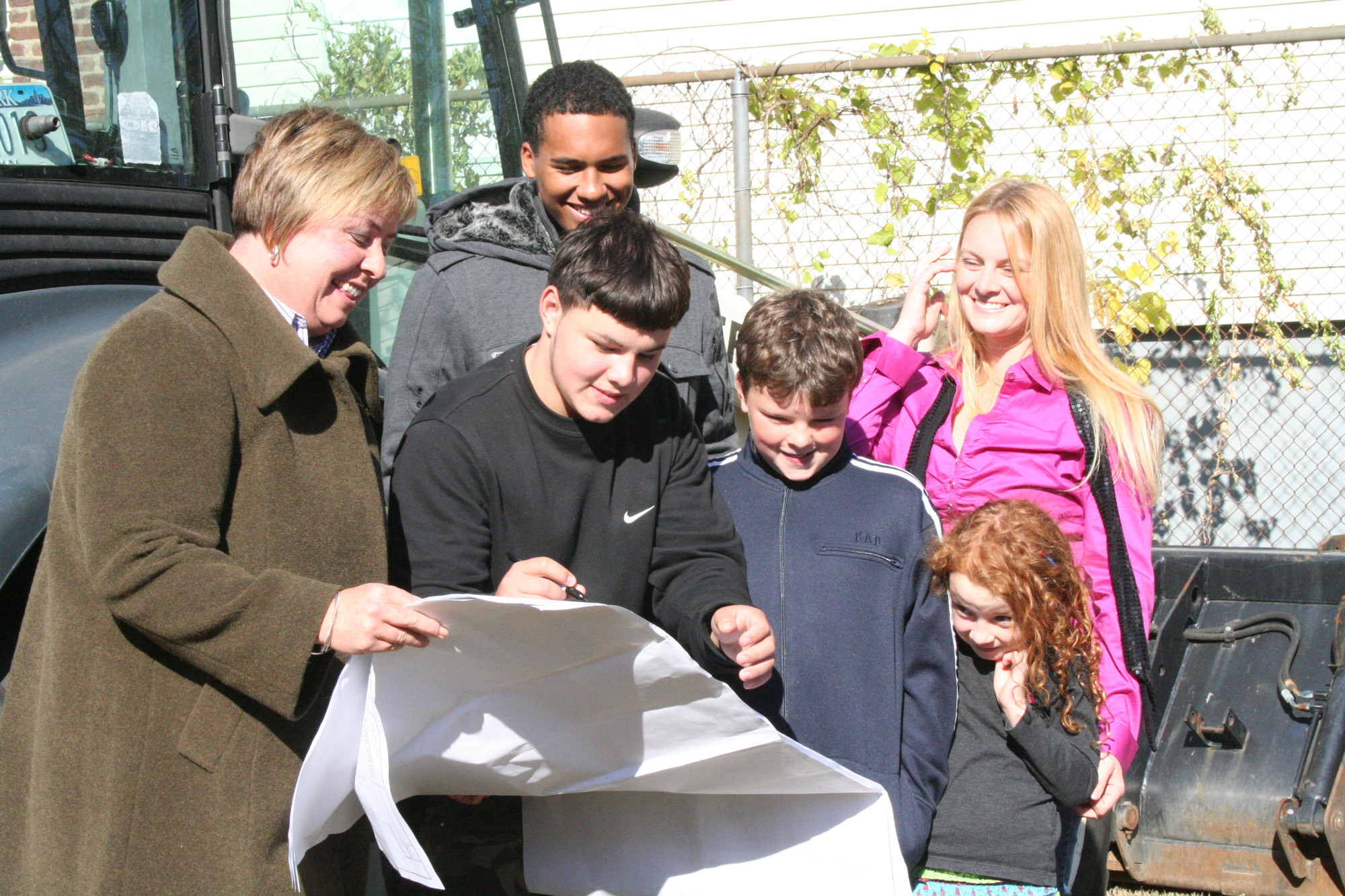 The McHale family, from top, Robert Jr., Daniel, Kaine, Heather and Kimberly, viewed the layout of their new house on Monroe Street, in Inwood, with Hempstead Town Supervisor Kate Murray.