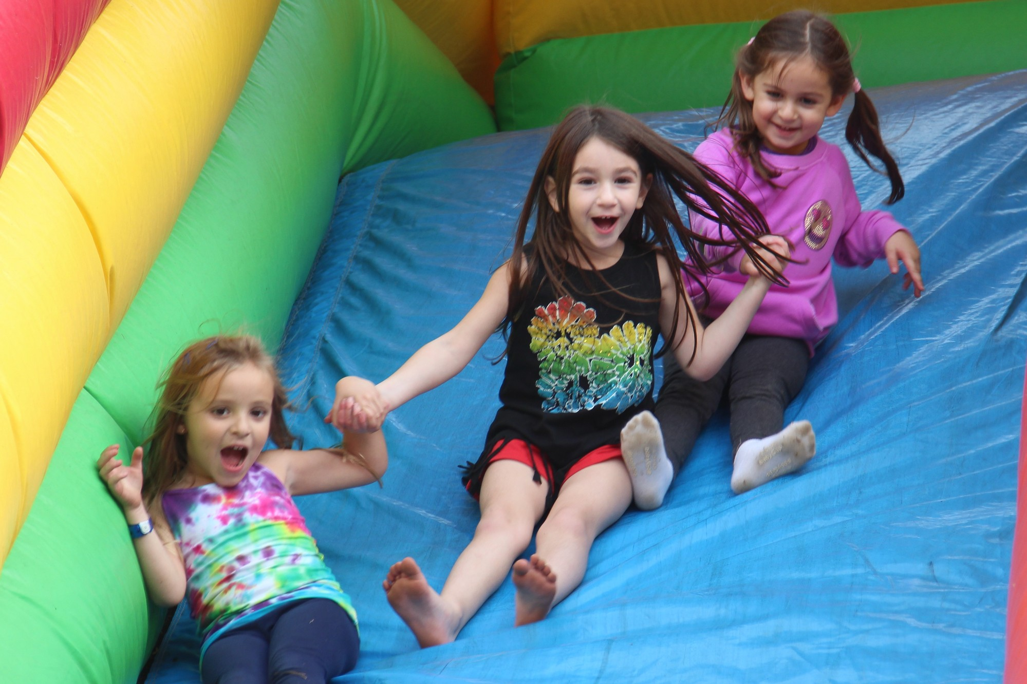 Going down the big slide was a lot of fun for three young girls, including Logan Sheflin, far left.