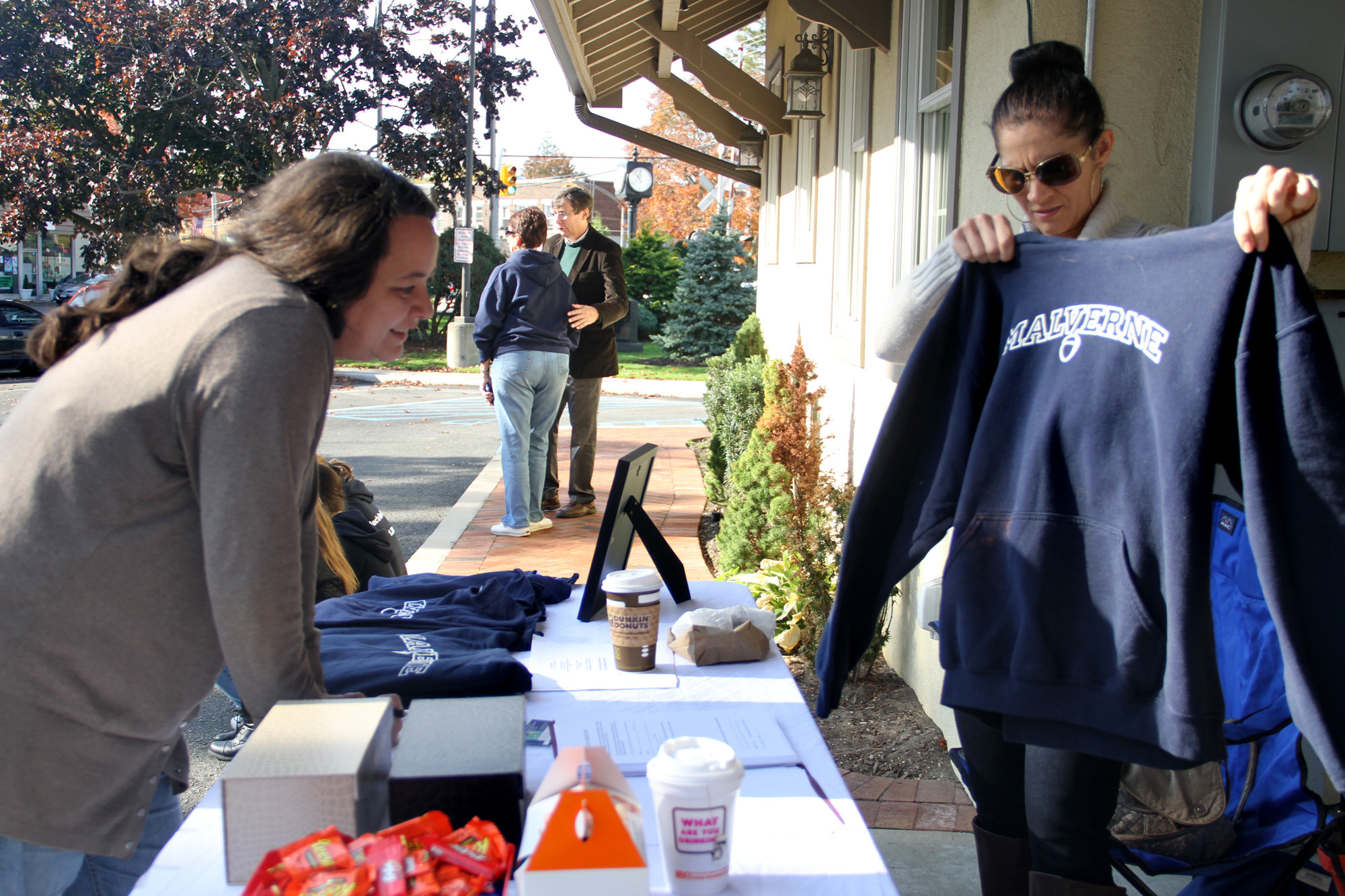 Malverne Civic President Suzanne Parra showed Laura Fiorino some of the Malverne merchandise on sale at the E-Cycle event on Nov. 2.