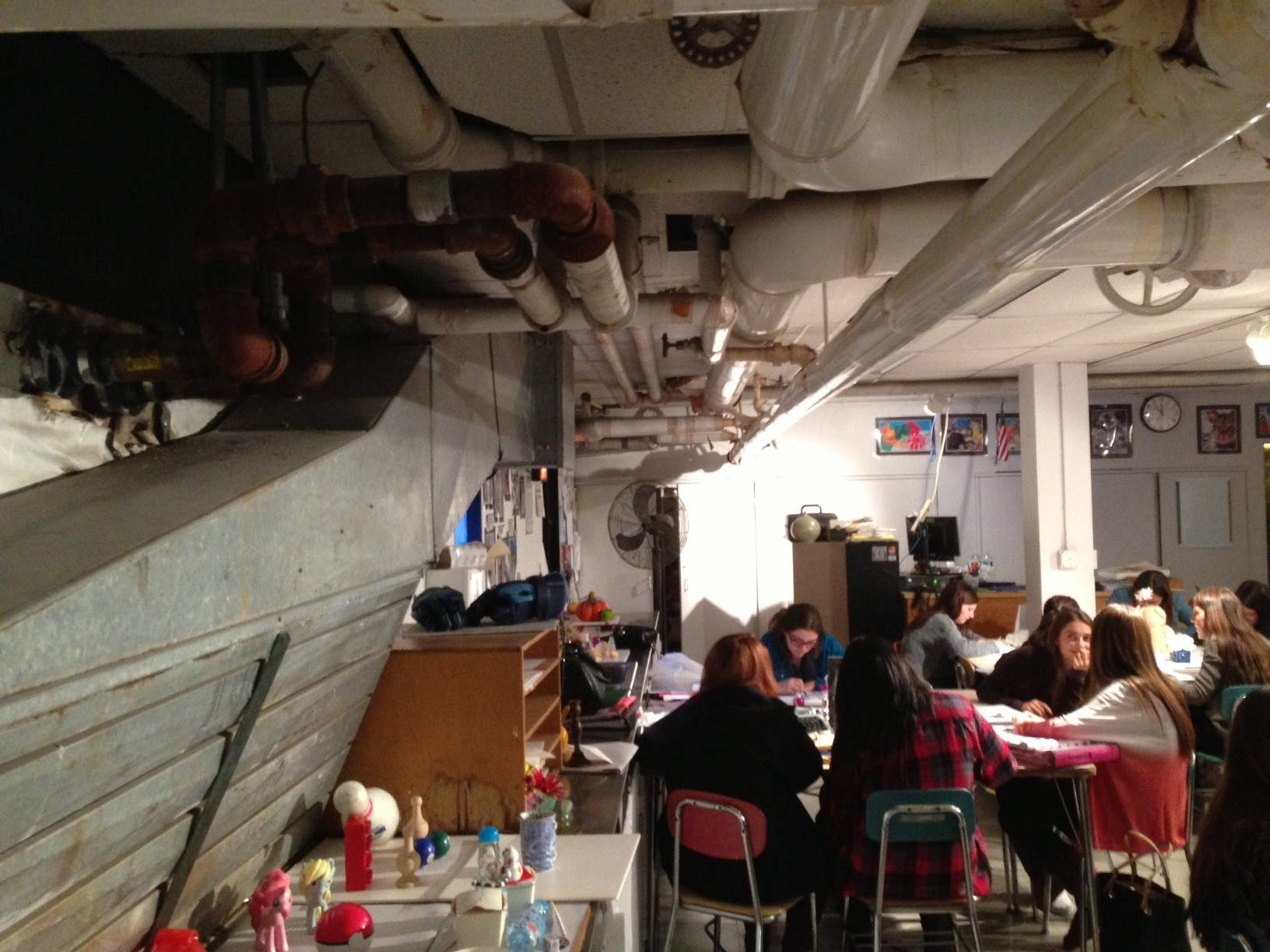 Mepham students take art in the basement, with heating and water pipes overhead.