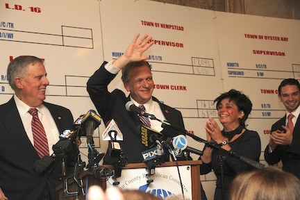 County Executive Ed Mangano waves to supporters from the podium at GOP headquarters Tuesday night. County party chairman Joe Mondello is at left and Mrs. Mangano is at right.