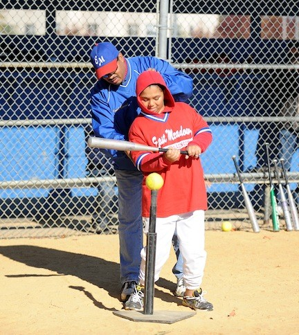 Gerard Rennie, a coach in the East Meadow Little Leagues Challenger Division, helped his son Gerard Jr. hit a ball during a game on Oct. 27.