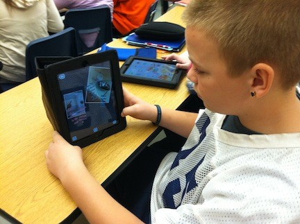 An Oceanside Middle School eighth grader works out a classroom assignment on his iPad.