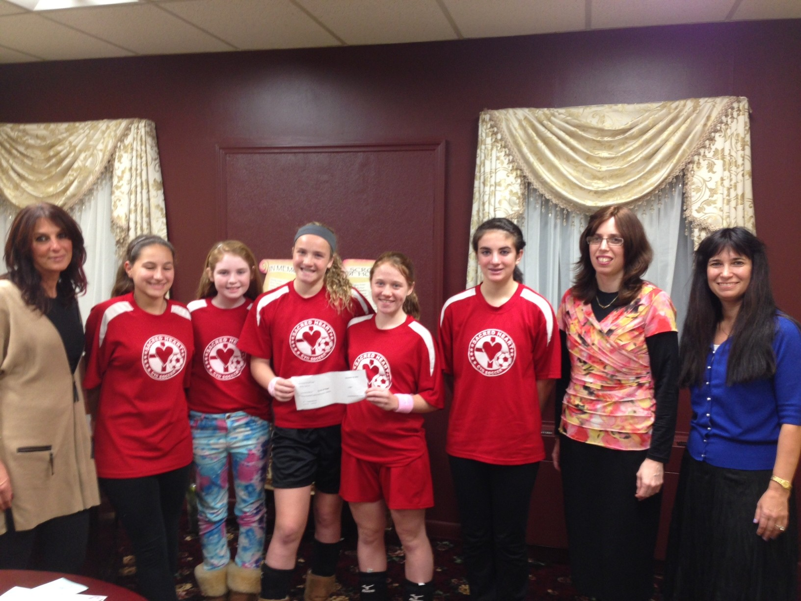 In October, the Sacred Heart girls raised money for Circle of Hope, a breast cancer support group. Above were, from left, Circle of Hope co-founder Lisa Fessler, Sacred Heart team members Allie Fiederlein, Elizabeth Collins, Tara Hagerty, Annie Coogan and Alexandra Brinton, Chanie Kramer, Chabad's program director, and Michele Krebs Muscovitz, Ciricle of Hope's coordinator.