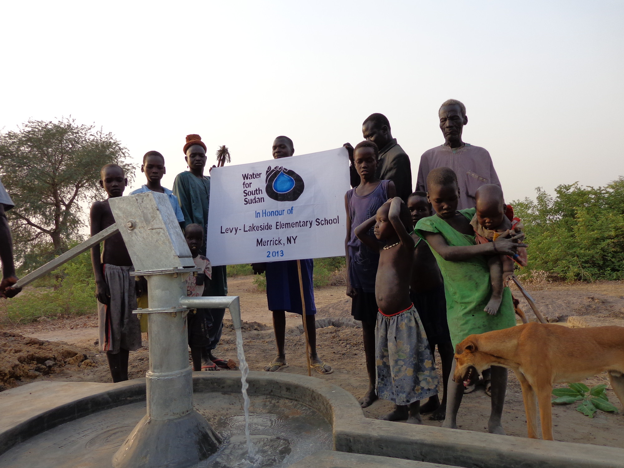 Residents of Gogrial East County, Warrap State, South Sudan held up a banner celebrating the contribution of students at Levy-Lakeside Elementary School in funding a drinking-water well at Manyang Primary School.