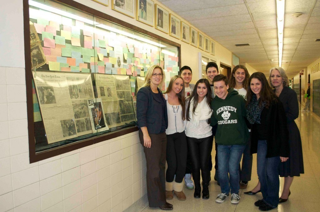 "Lisa Scherer, a John F. Kennedy High School social studies teacher, left, and Karen McGuinness, the social studies department chairwoman, right, joined seniors from Kennedy High School's ""Participation in Government"" class in front of a display commemorating President Kennedy's life and legacy on the 50th anniversary of his assassination."