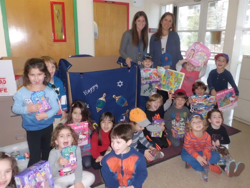 HAFTR nursery school students helped with collecting about 200 toys that will be donated to OHEL Children's Home and Family Services and given to those in need. Standing were teachers Dara Karhu and Debbie Ozer.