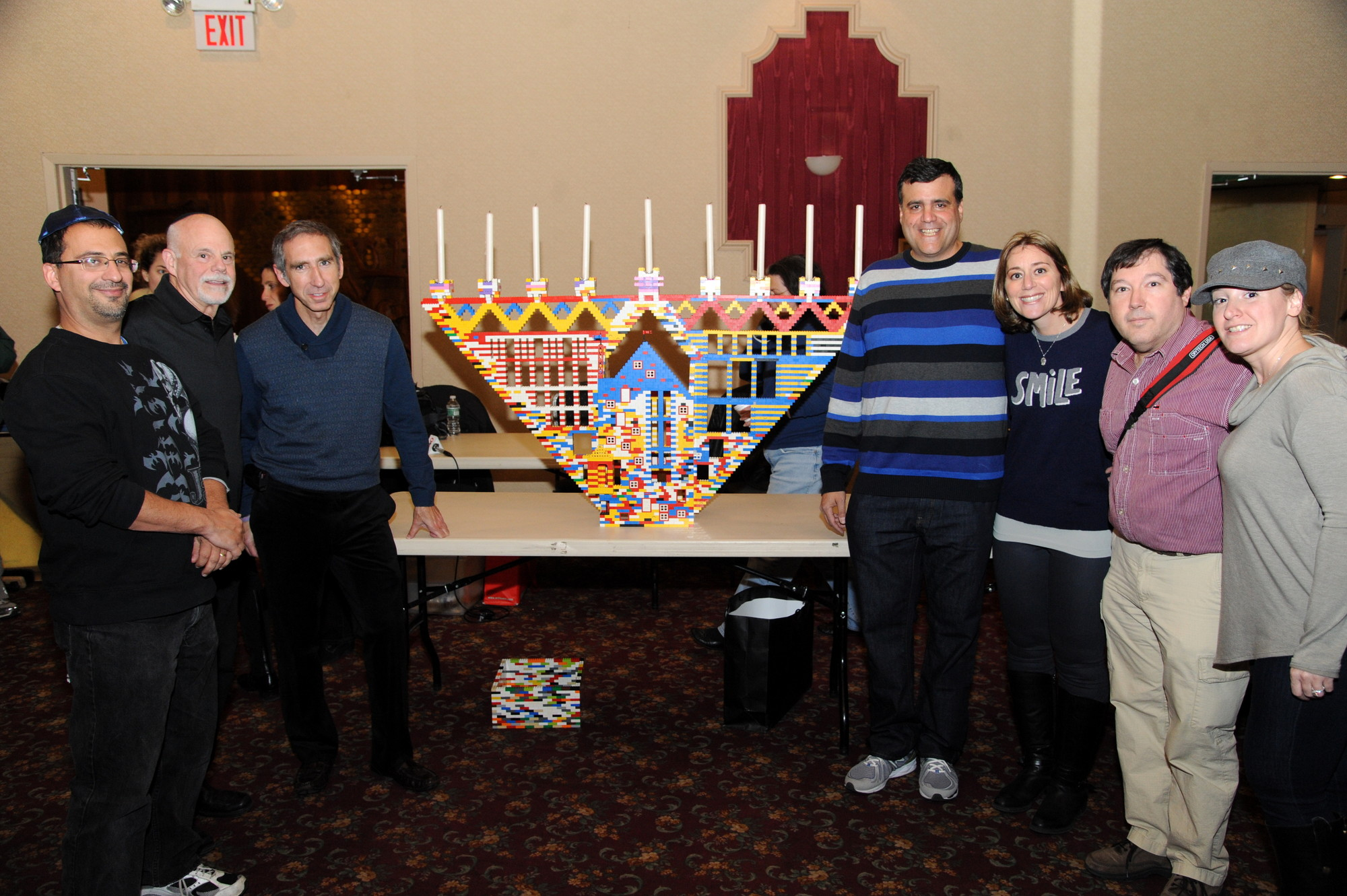 Peter Bloch, Stephen Schwartz, TISO Rabbi Scott Hoffman, Curtis Izen, Lori Izen, Bruce Feingold, and Ali Goldsmith stood for a photograph beside what eventually became the head of a giant LEGO menorah.