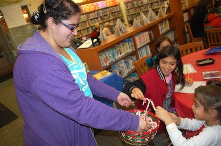 Library page Kayla Serpa handed out candy canes to sisters Isabella, 10, and Christiana Santos, 5.