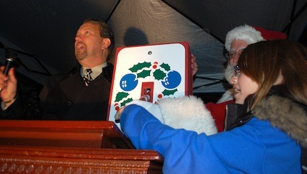 Mayor Ed Fare and Mayor for a Day contest winner Ariela Hulsen pulled the switch to light the Christmas tree located behind Village Hall.