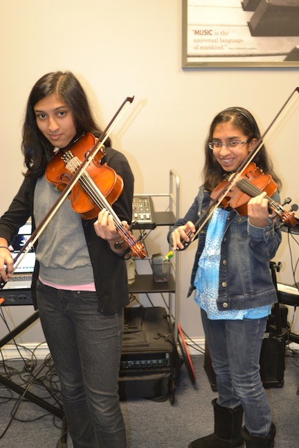 Binita Shah, 16, of W.T. Clarke High School, left, with sister Aashini Shah, 13, of Clarke Middle School, during a recent rehearsal.