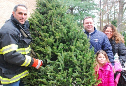 Ron Luparello, left, the Merrick Fire Department�s public information officer and a former chief, helped the Goldstein family of Bellmore, including Andrew, his wife, Susan, and their daughter, Makenzie, select the perfect tree.