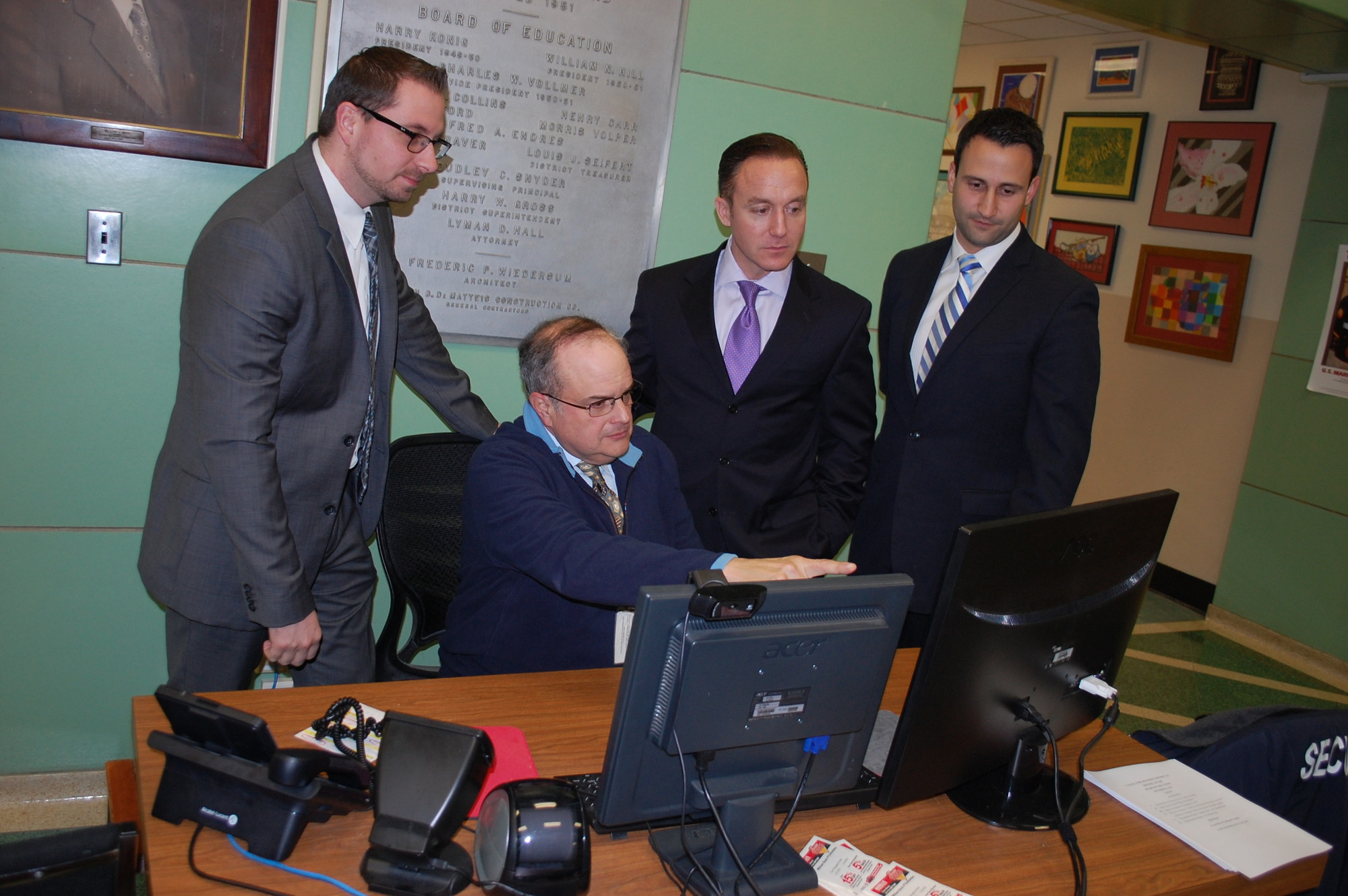 John Venza, one of District 24's security guards, looked over the new monitoring system at the William L. Buck School with principals, standing from left, Mark Onorato, Dr. Scott Comis and Rosario Iacono, before the Dec. 12 board meeting.