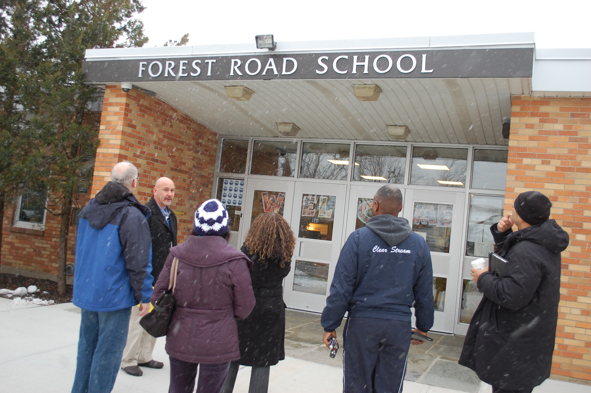 District 30 officials looked at the new sign above the entrance to Forest Road School during last Saturday's building tour.