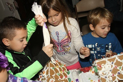 Angelo Forthofer, 6, joined by cousins Riley, 6, and Patrick  Forthofer, 4, work as a family on their gingerbread houses.