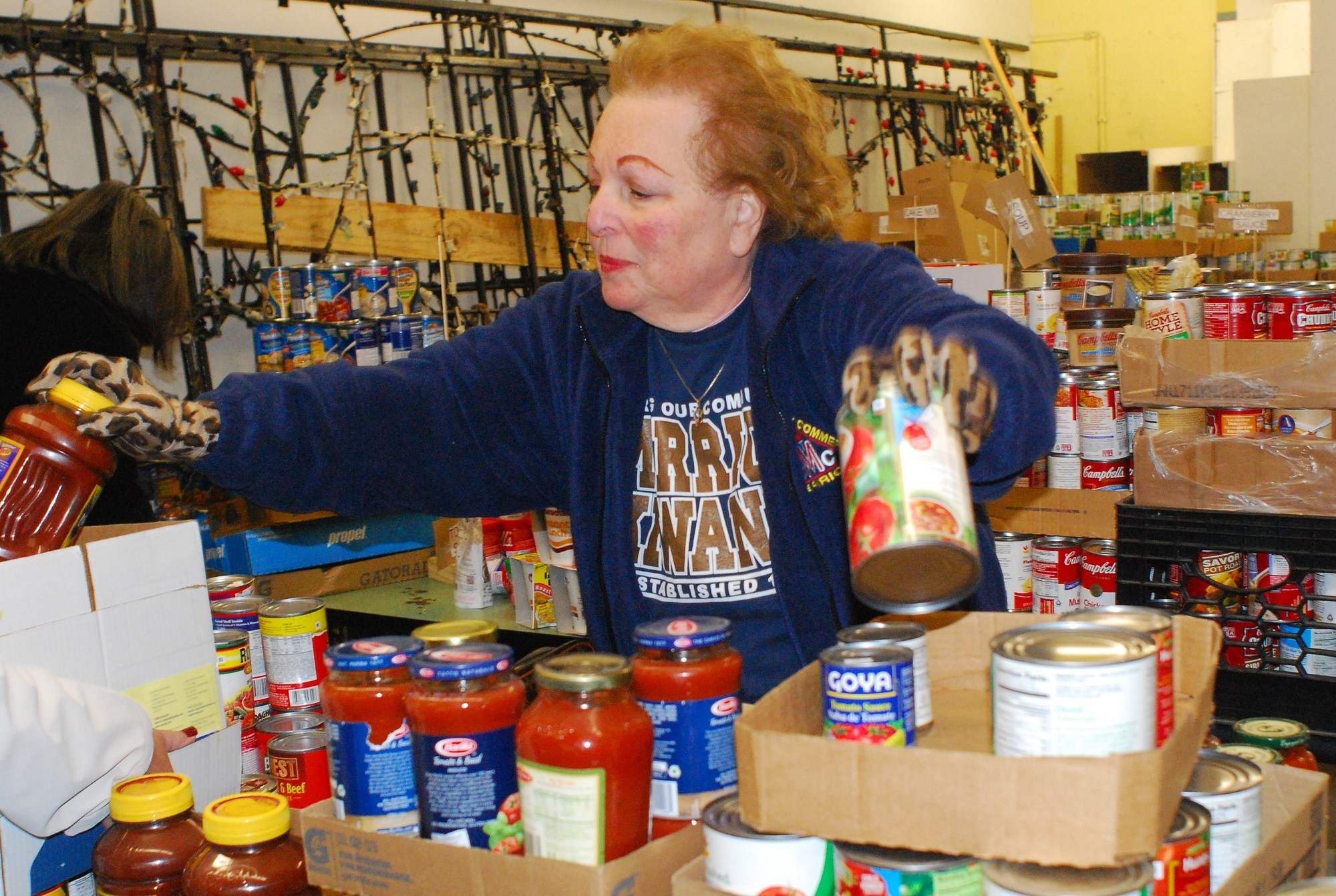 Merrick Kiwanis Club volunteer Susan Helsinger was at the front of the line assembling boxes of food for donation to local families in need.