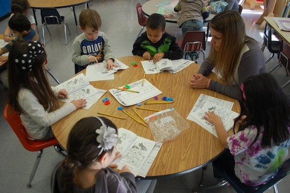 Kindergarten teacher Gail Shaw helps students read basic sentences during a guided reading exercise.