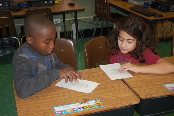 "Howell Road School fourth-graders Christopher Shavuo, left, and Benjamin Bustamonte study the poem ""Saturdays."""