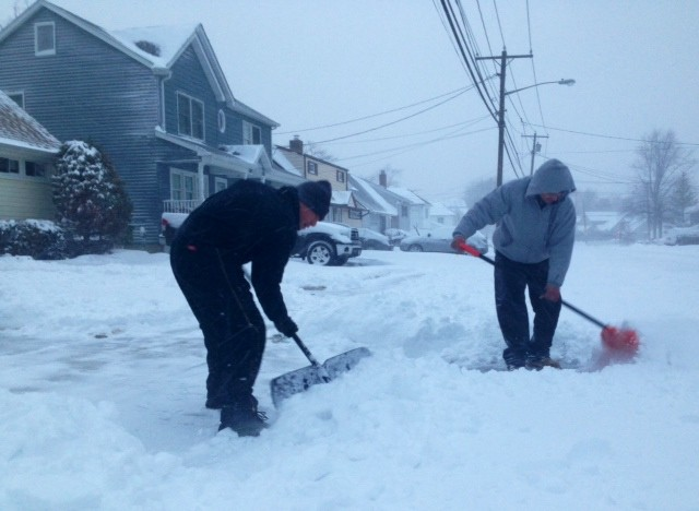 With temperatures hovering in the mid-teens, Jonathan Rodrigues and Jose Mancia shovel out a Beach Drive home in Merrick at 7:15 a.m. on Friday.