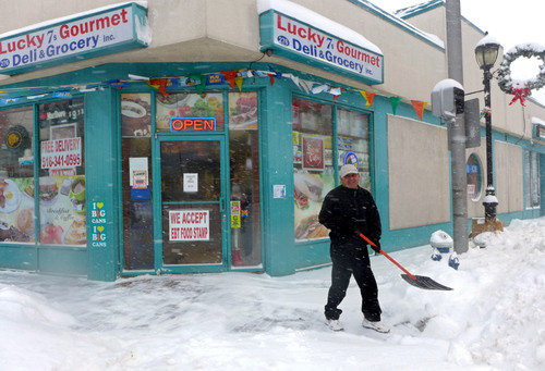 Clearing the sidewalk in front of Lucky 7s Gourmet on the corner of Atlantic and Centre avenues in East Rockaway.
