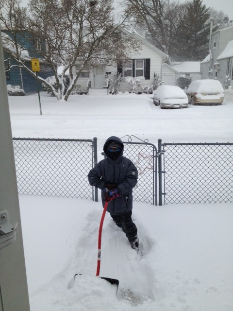 Kyle Bergin bundled up and shoveled snow on Central Avenue in Lynbrook.