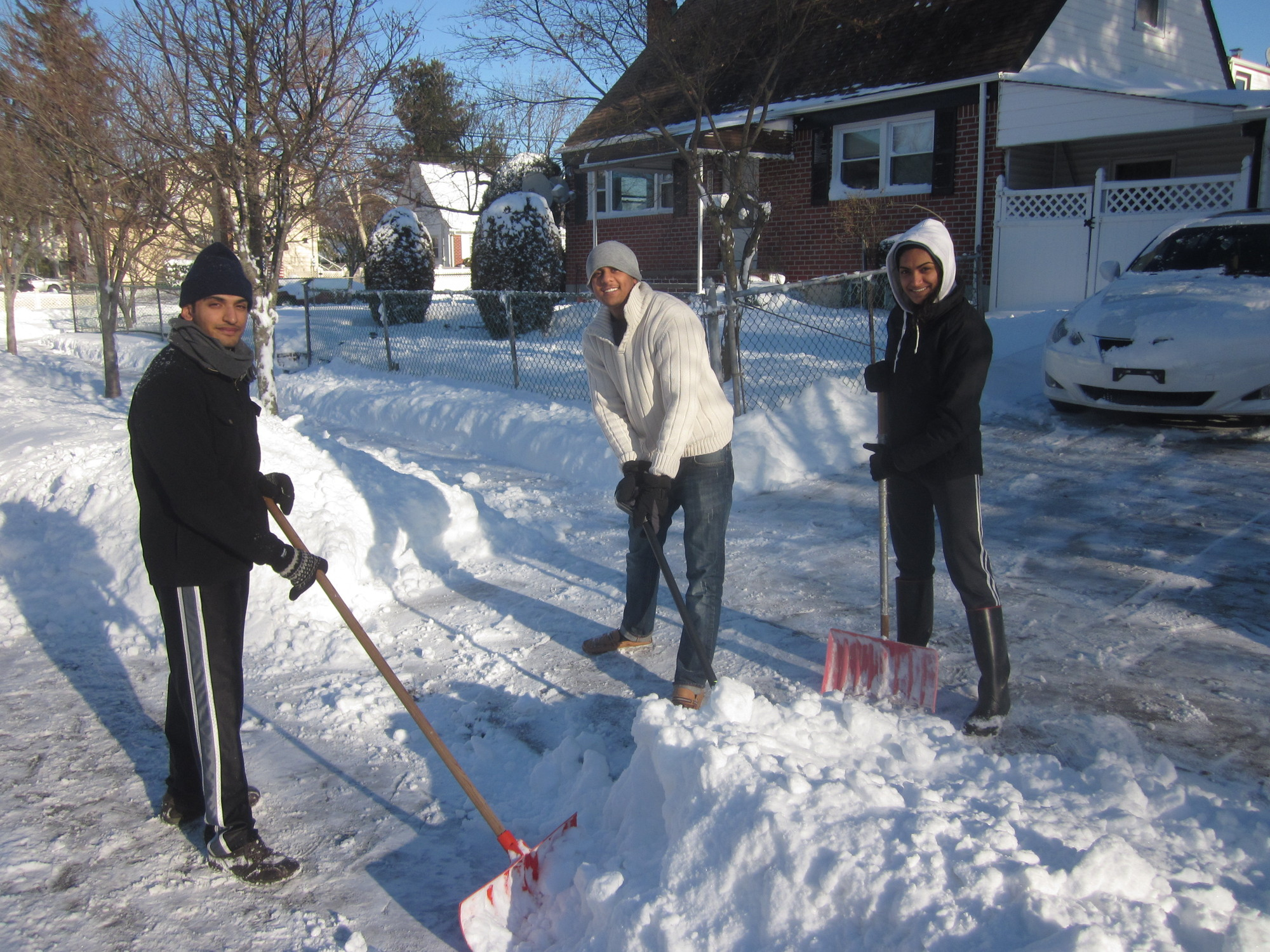 The Patels, from left, Ajay, Dave and Nilam made shoveling a family activity in front of their Lincoln Avenue home.