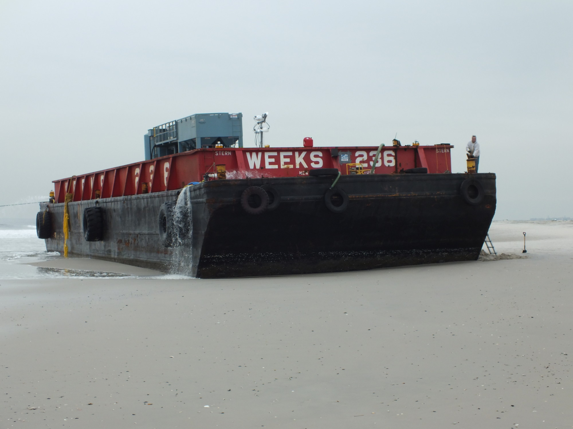 The 250-on barge that ran aground on Silver Point County Park in Atlantic Beach was being pulled back into the water by two tugboats on Thursday.