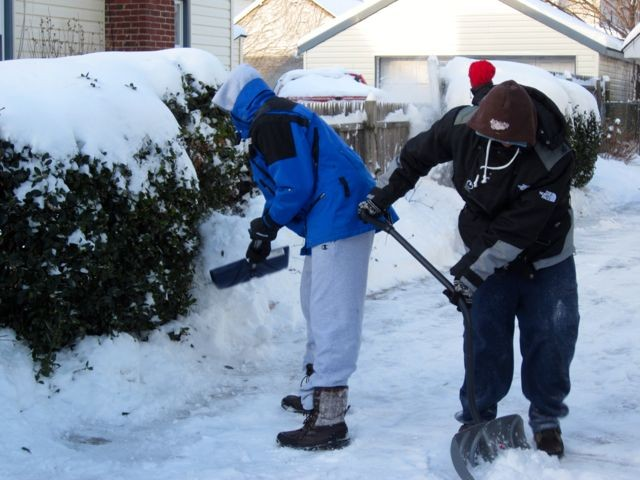 From left, bundled-up residents Pace Shaw and Keith Pfifer shoveled out a home on Madison Avenue, with help from Jordan Smith, rear.