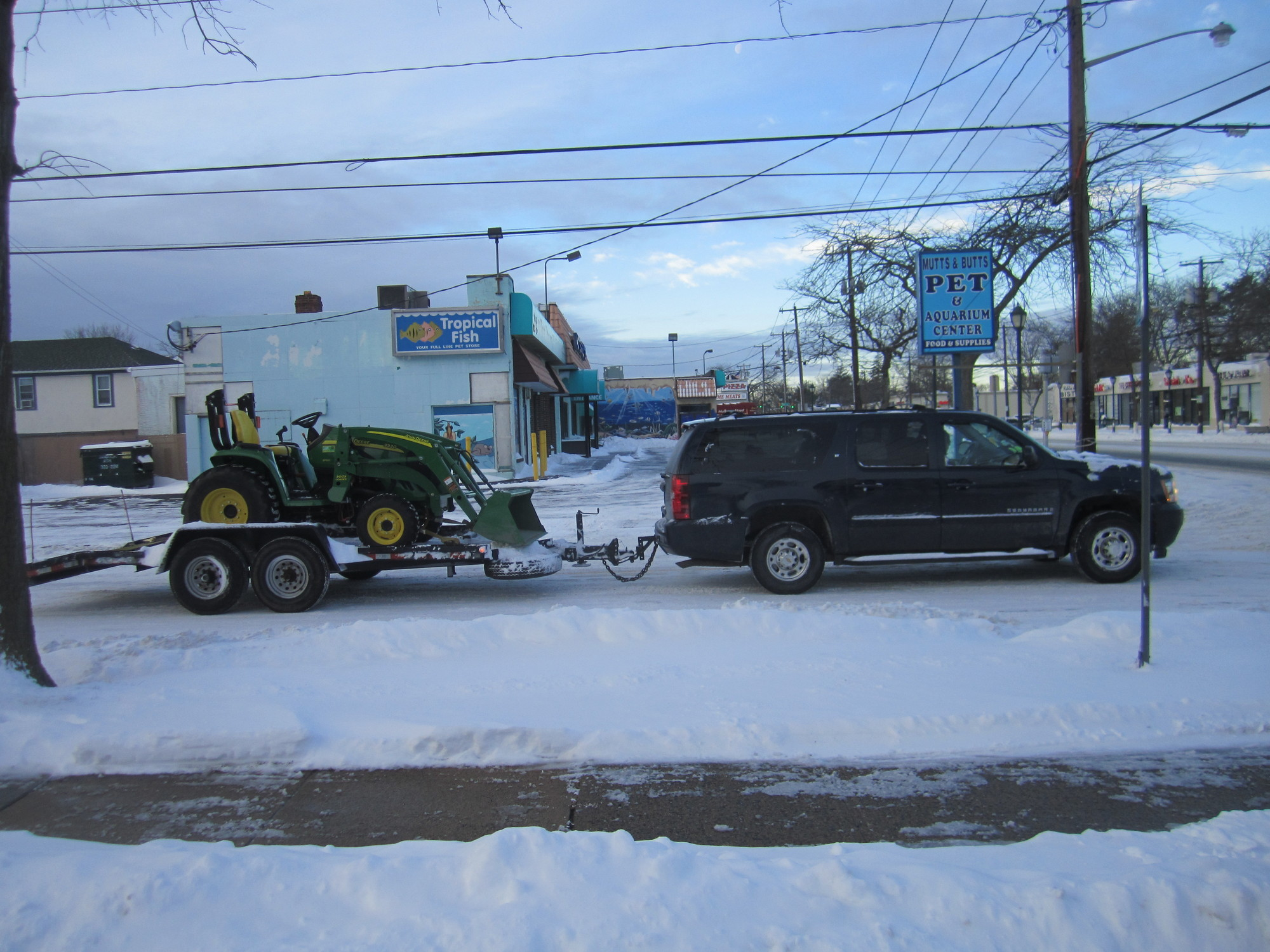 "A SUV on snowy roads in Merrick hauled a plow past a pet store sign that advertised ""tropical fish."""