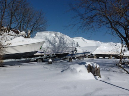 Boats collected snow along the docks on Mott Street, idly waiting until they ride again this summer.