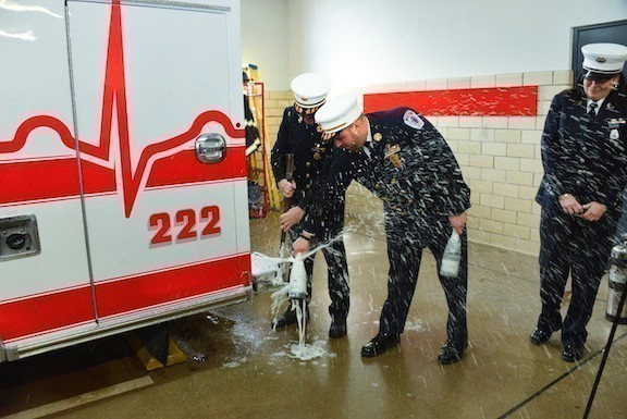 Former chief and current Captain Fran Eye, left, and Chief Anthony D'Esposito broke a champagne bottle to officially welcome the department's new ambulance last Sunday, as Lieutenant Margaret Rodriguez looked on.