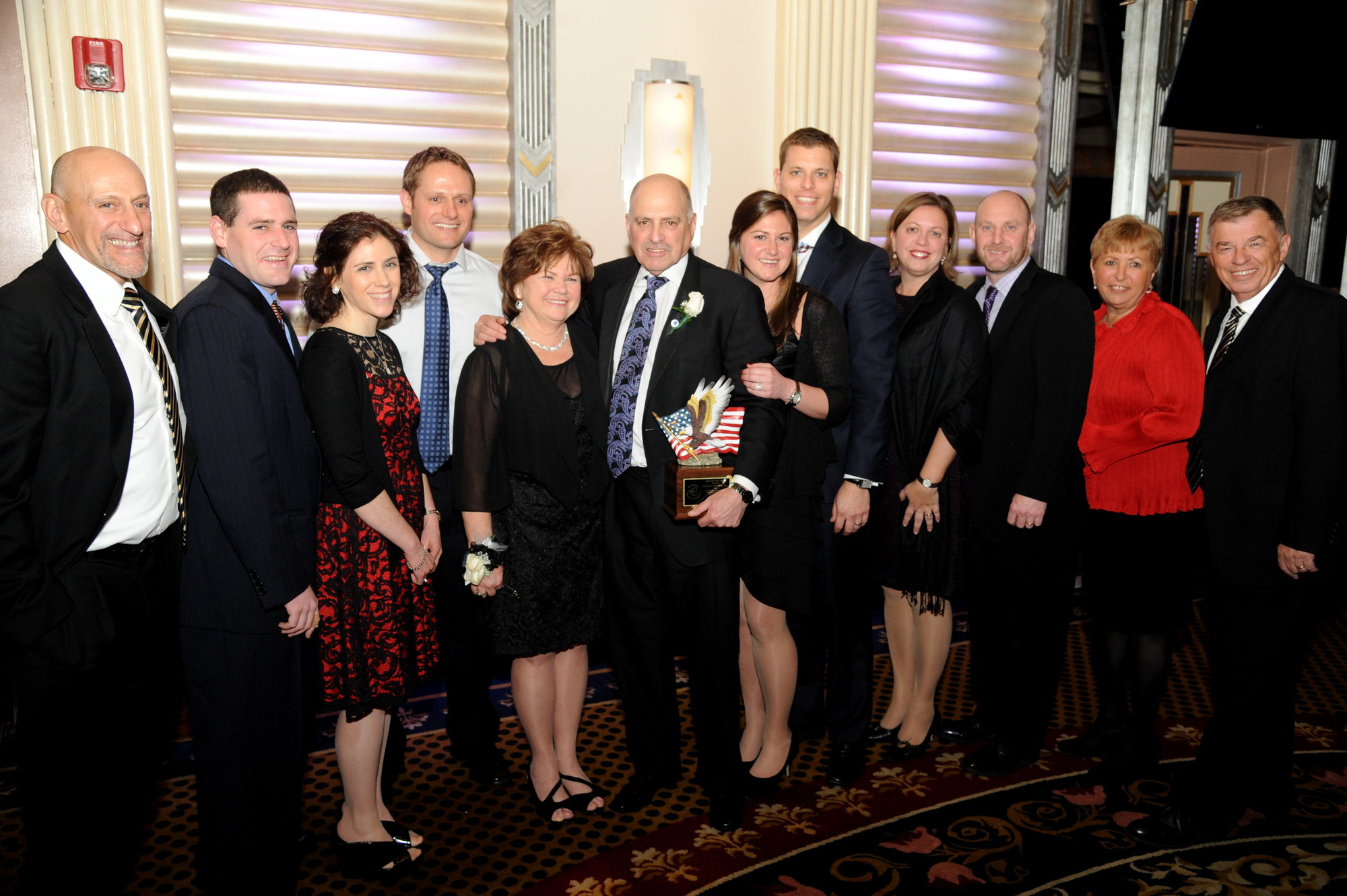 Alan Hodish, sixth from left, was honored as Man of the Year. He was joined to his right by his wife, Denise, and the rest of his family and friends.