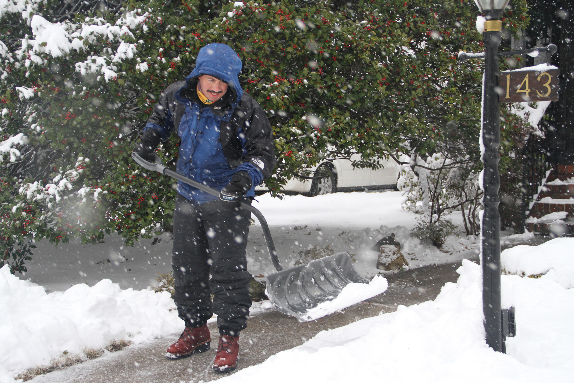Rich Spero cleared his parents' walkway in Malverne as the snow fell on Monday.