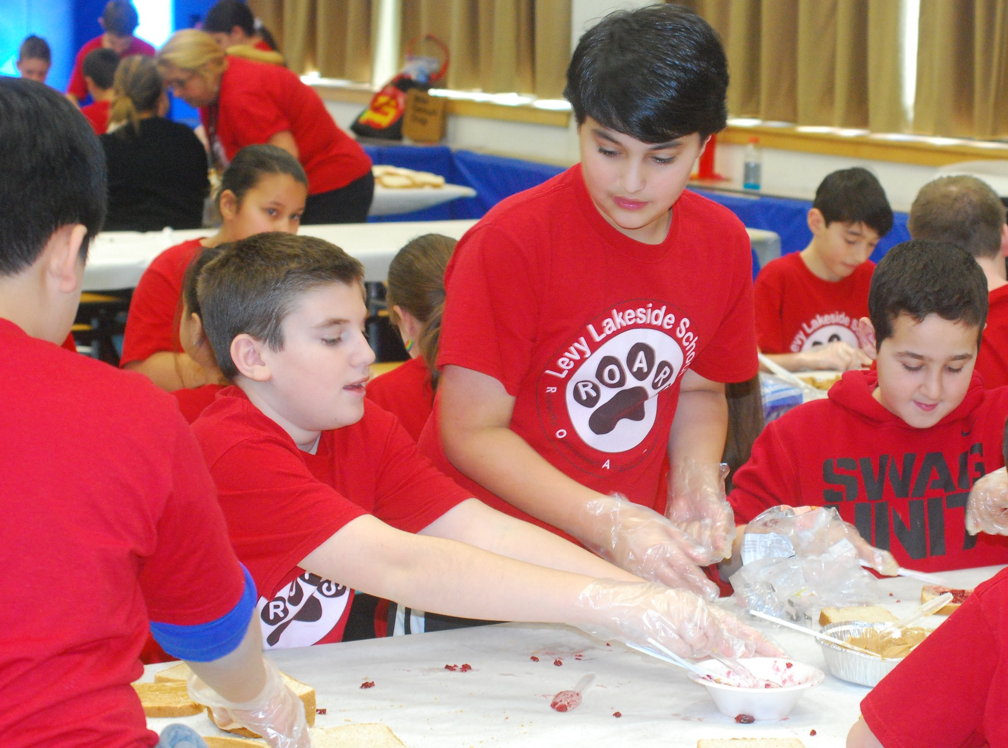 Levy-Lakeside Elementary School sixth-graders made more than 2,000 sandwiches for the homeless last Friday afternoon. Above, Ross Oginsky, from left, Josh Wolk and Tamer Eldidi hard at work.