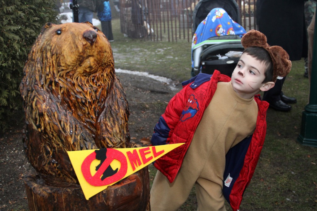 Justin Nealia, dressed in his own groundhog costume, peeked at a wood-carved Mel sculpture after the real critter predicted an early spring at the Village of Malverne's 19th annual Groundhog Day ceremony at Gazebo Park on Sunday.
